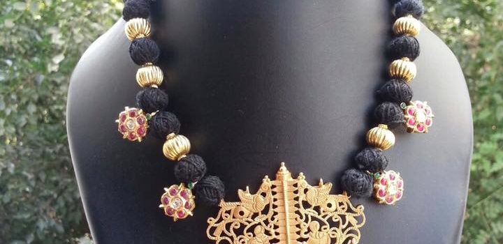 black thread necklace with gold filigree pendant